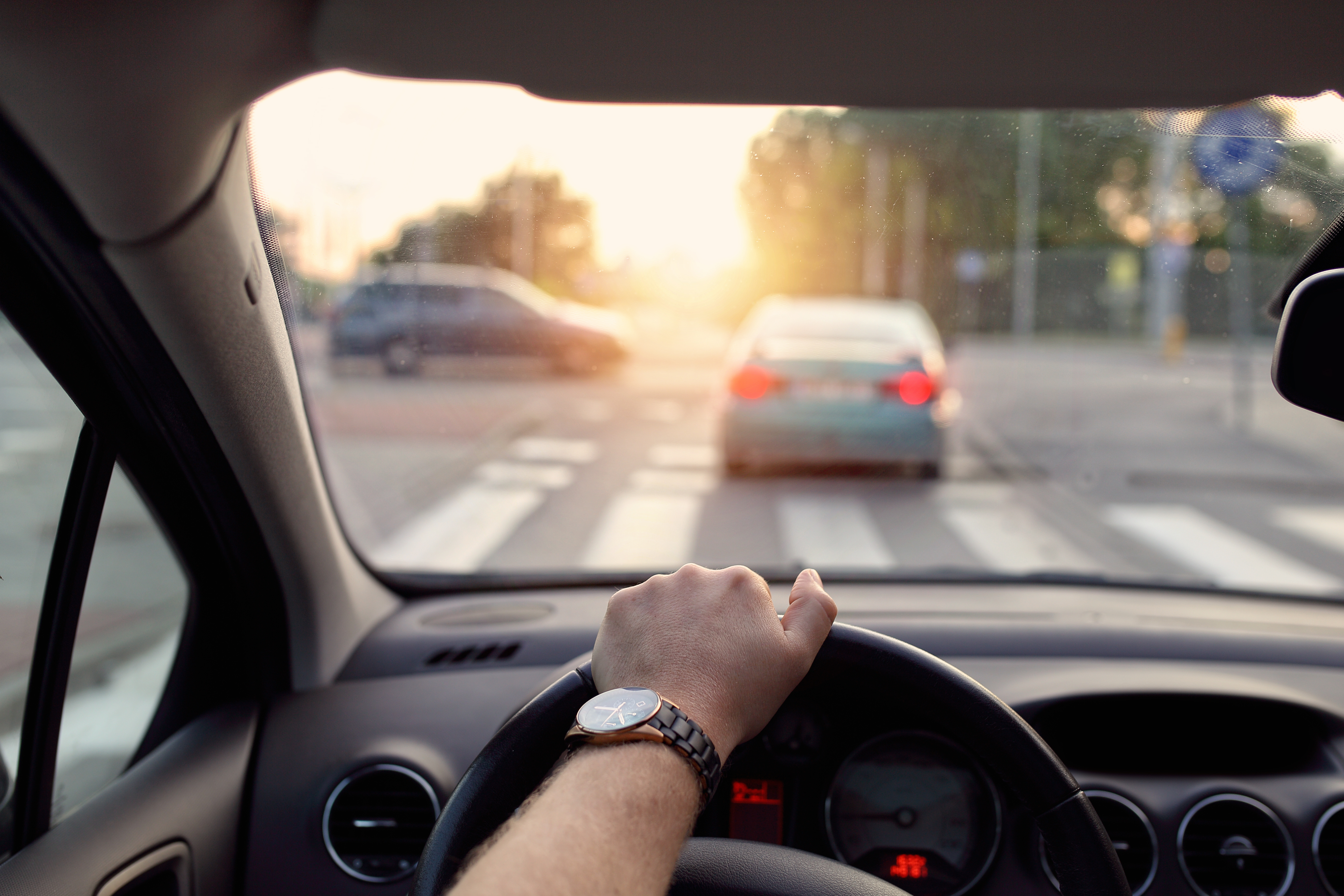Aus der Sicht des Autofahrers, Blick auf das Lenkrad und die Straße -  Unternehemensgruppe HEITZIG & HEITZIG berät Sie bei der Umstellung auf Elektromobilität
